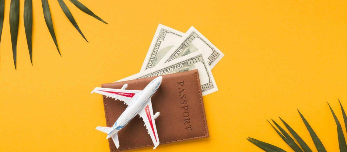 flat-lay-passport-with-money-plane-figurine-top